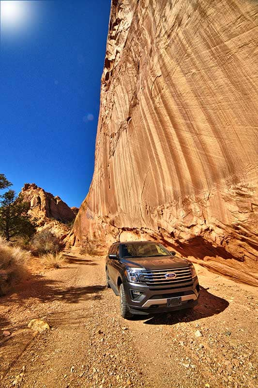 Water Pocket Adventures SUV on a dirt road next to tall sandstone cliff