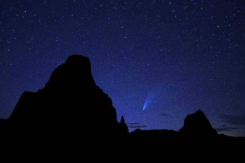 Night sky photo from the desert showing stars and a comet