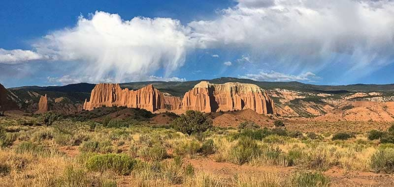 Photo of Cathedral Valley in bright sunshine with wispy clouds in the blue sky.