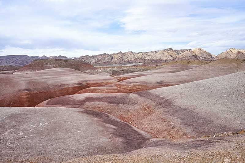 Photo of sandstone dunes in the foreground and more sandstone formations in the background