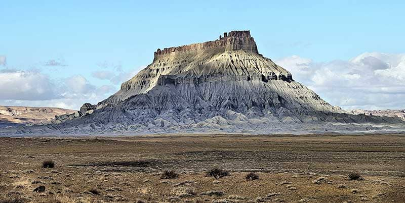 Standalone sandstone formation rising up from the desert floor