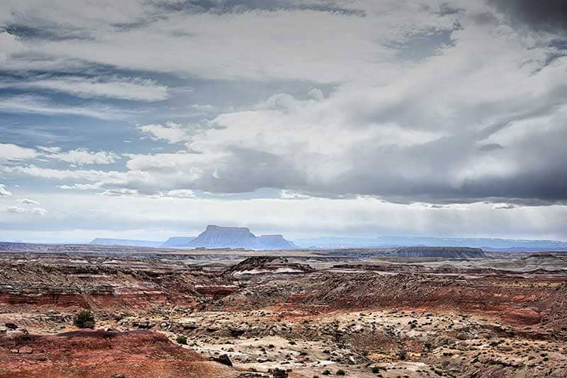 Panorama of the desert with large sandstone formations in distance with sunshine and clouds