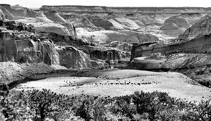 Black & White photo of sandstone cliffs showing many layers and colors of sandstone