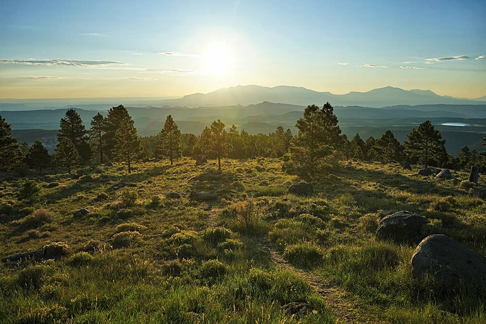Photo looking across a large valley to mountain ranges in the distance at sunset