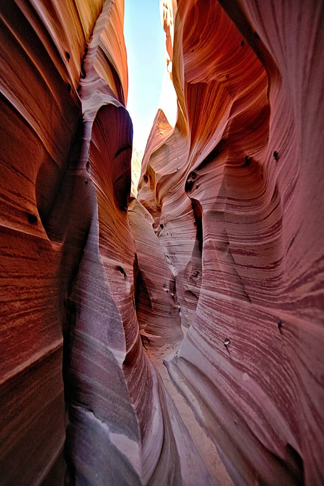 A view through a narrow slot canyon with textured sandstone walls